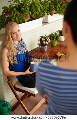 Young blonde woman chatting with female friend at balcony, drinking tea. - stock photo