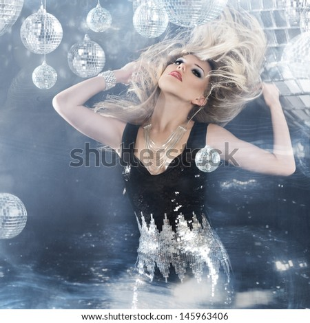 Young blonde woman dancing at night disco club. Motion blur - stock photo