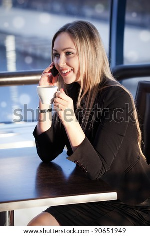 Young blonde woman drinking tea in the cafe