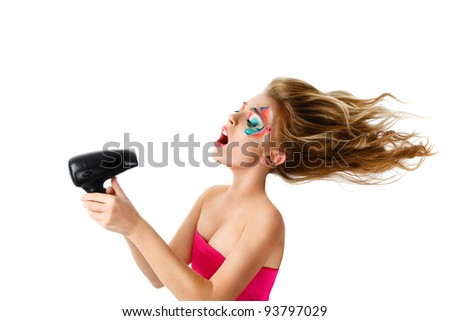 Young blonde woman drying hair with electric fan