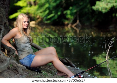 Young blonde woman fishing from bank of creek - stock photo