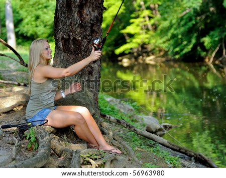 Young blonde woman fishing on creek bank - casting - stock photo