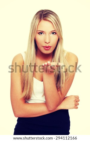 Young blonde woman giving kiss - stock photo
