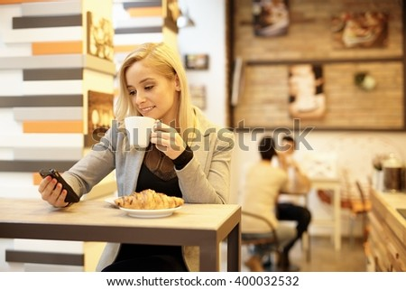 Young blonde woman having breakfast in cafeteria, reading text message on mobilephone. - stock photo