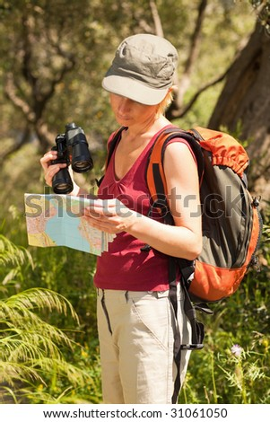 young blonde woman hiking and reading map. - stock photo
