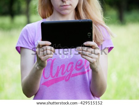 Young blonde woman holding a tablet outdoors, looking at the screen, green background - stock photo