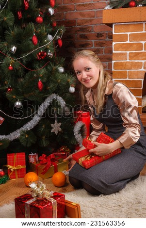 Young blonde woman in a business attire sorting through the presents under the Christmas tree - stock photo