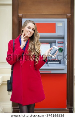 Young blonde woman in a red coat withdraw cash from an ATM in a shopping center - stock photo