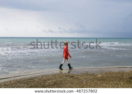 young blonde woman in a red raincoat and dark blue rubber boots walks on the shore of the stormy sea