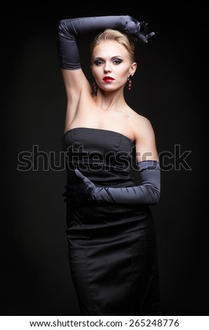 Young blonde woman in black dress and long gloves on dark background - stock photo