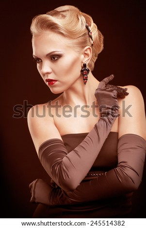 Young blonde woman in black dress and long gloves on dark background toned in marsala color