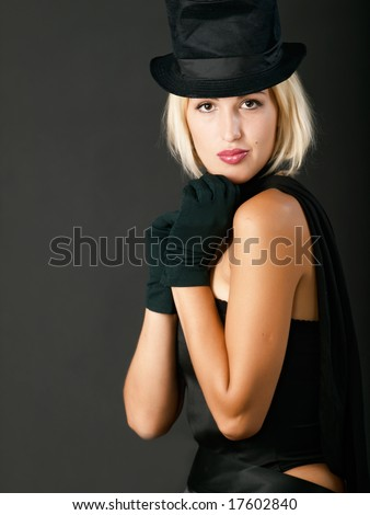 Young blonde woman in black hat looks and clasp arms to one's chin.