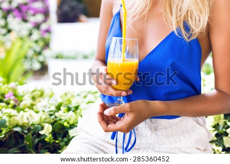 Young blonde woman in bright sexy top holding fresh tasty mango juice, relax and enjoy her brunch. flowers on background. - stock photo