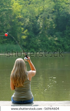 Young blonde woman in denim shorts fishing from river dock - casting - stock photo