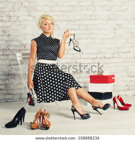 Young blonde woman in fashioned dress sitting in a chair in the store and choosing shoes (make shopping) - stock photo