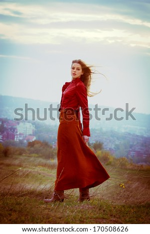 young blonde woman in long red skirt and leather jacket stand in the wind on hill above the city