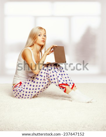 Young blonde woman in pyjamas on white whole-floor carpet browsing laptop  near window - stock photo