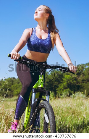 Young blonde woman in sport wear posing, outdoor on the bicycle