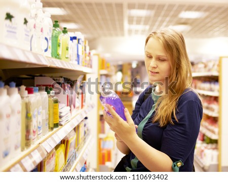 Young blonde woman is reading inscription on the cleaner bottle in the supermarket - stock photo