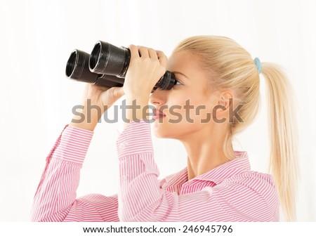 Young blonde woman looking through binoculars. - stock photo