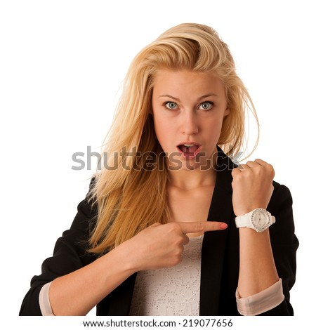 Young blonde woman looks at her watch when she is being late isolated over white background - stock photo