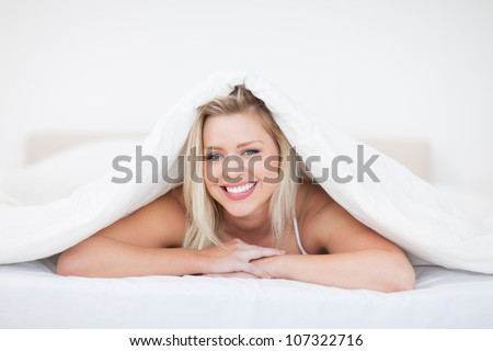 Young blonde woman lying under a duvet in a bedroom - stock photo