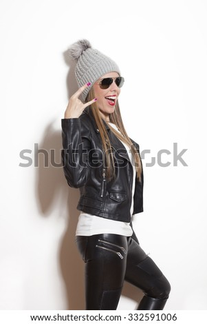young blonde woman making faces and gestures, wearing sunglasses cap black leather jacket and leggings, studio white
