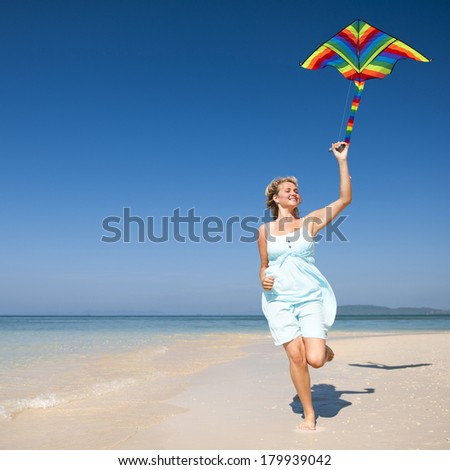 Young Blonde Woman Playing With a Kite On a Beach - stock photo
