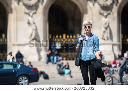 Young blonde woman portrait in front of Opera theater in Paris, France.
