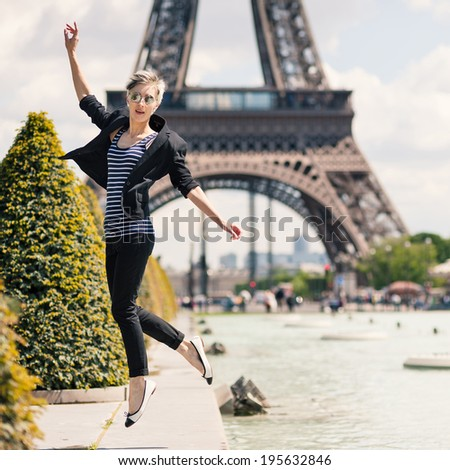 Young blonde woman portrait jumping in front of the Eiffel Tower in Paris, France.  - stock photo