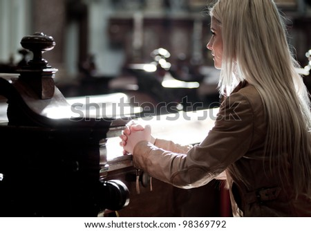 Young blonde Woman praying in the Church - stock photo