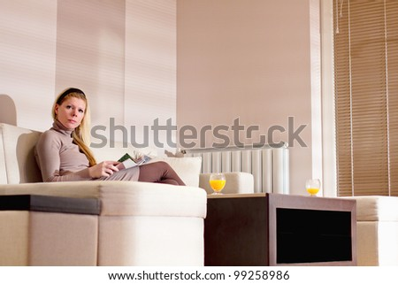 Young blonde woman relaxing at home, reading magazine - stock photo