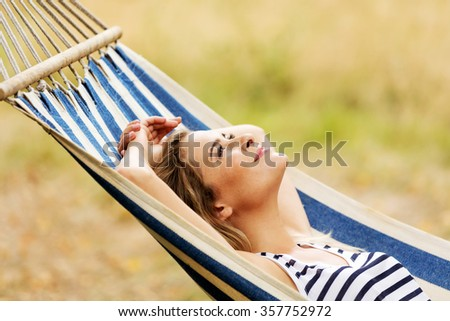 Young blonde woman resting on hammock.