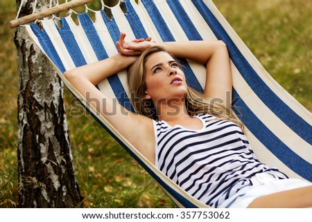Young blonde woman resting on hammock. - stock photo