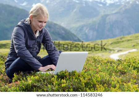 young blonde woman sits with laptop in alpine meadow before mountain landscape - stock photo