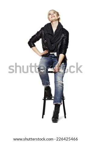 Young blonde woman sitting on high stool and looking up. Isolated on white background. - stock photo