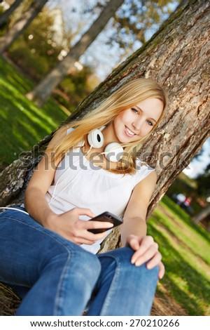 Young blonde woman sitting with smartphone and headphones in summer in a park - stock photo