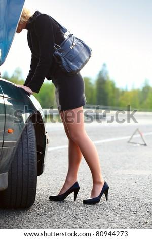 Young blonde woman standing by broken car and looking to engine - stock photo