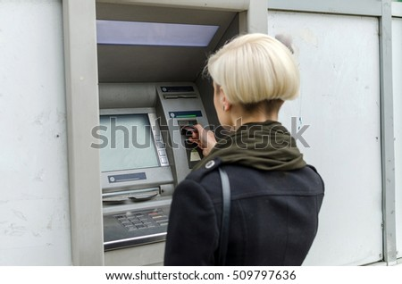 Young blonde woman using cash machine on the street