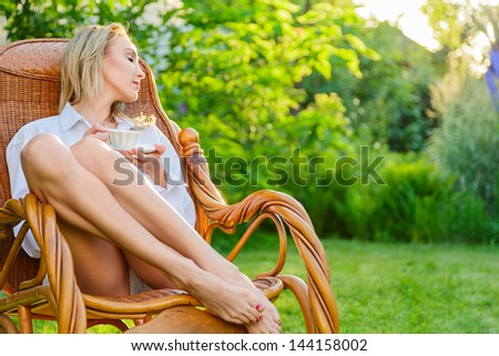 Young blonde woman wearing in man's shirt relax at outdoor sitting on a rocking chair holding tea cup - stock photo