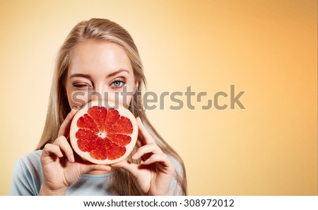 Young blonde woman with grapefruit in her hands studio portrait isolated on orange background. Young blond woman showing OK sign about the benefits of vitamin C - stock photo