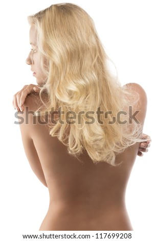 young blonde woman with naked torso and long wavy hair, looks at left and has the right hand on the left shoulder