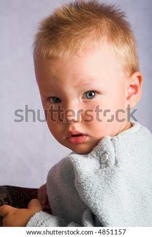 Young blue-eyed child in blue shirt at the gray background