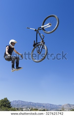 young BMX cyclist falling down from air with his BMX bike on a BMX session in the mountain - focus on the left arm - stock photo