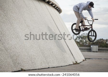 Young bmx rider doing a wallride with a 360 out