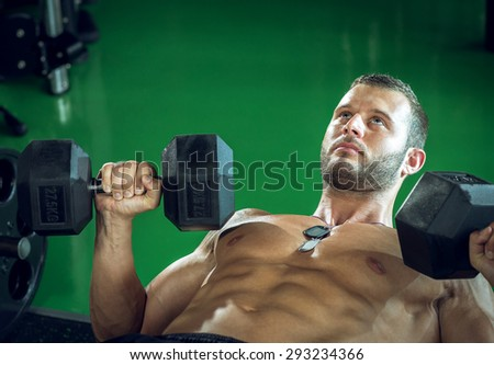 Young bodybuilder doing biceps curls and press while lying down. - stock photo