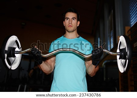 Young bodybuilder doing exercises with dumbbell in gym, muscular build man pumping up muscles with dumbbell, attractive young man training indoor