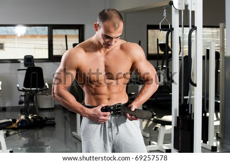 young bodybuilder girding on his bodybuilding belt - stock photo