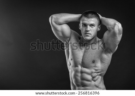 Young bodybuilder guy in good shape against a dark background. Man posing, showing his muscle definition.