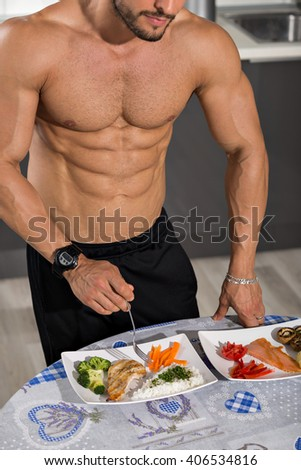 young bodybuilder in the kitchen with two plates of healthy food: rice, chicken grill, broccoli, carrots, mushrooms, salmon, tomato, red peppers - stock photo